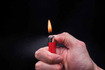 European white mans hand holds a burning red ignited plastic gas lighter with fire on an isolated black background Banque d'images