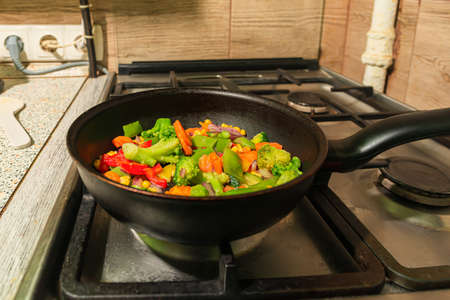 Many different colorful vegetarian vegetables are fried in a skillet pan on the kitchen stove. Peas, pisums, onions, peppers, capsicums, broccoli, corn and carrots 版權商用圖片