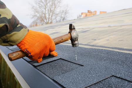 Rę ce rę ce pracowników montaż dachowych gontów bitumicznych. Młot pracownika w paznokcie na dachu. Roofer jest młotkiem paznokciowym w dachu półpasiec.