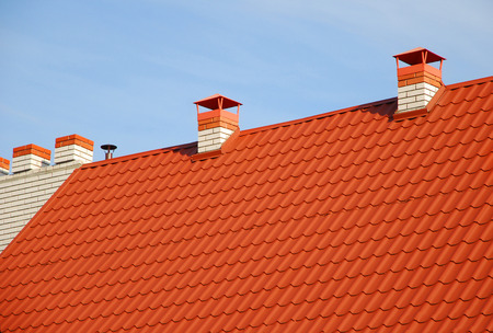 New red tiled roof with metal chimney house roofing construction exterior. Roofing construction. Close up on metal roofing with roof