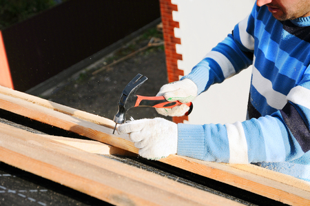 Builder Building Roof. Worker Hammer in Nails on the Roof. Roofer Hammering a Nail into the new Roof Beams.
