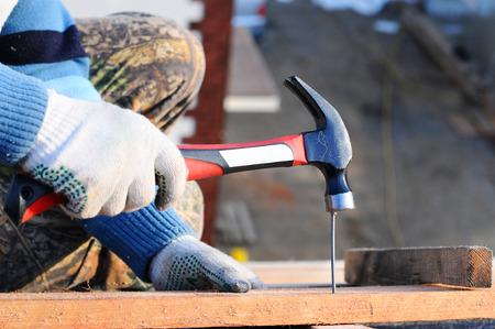 clavados: Trabajando en el techo. Trabajando mano martillos martillar un clavo. la instalación de aislamiento y la película de barrera de vapor. constructor trabaja en un techo. Constructor del trabajador clavado cubierta de vigas.