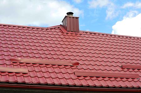Nahaufnahme auf neue Schornsteinrohr und Dach Schutz vor Schneebrett (Schneeschutz) auf den Hausbau. individuelle Heizung. Coaxialrohr Heizung Haus Coaxial Schornsteinrohr.