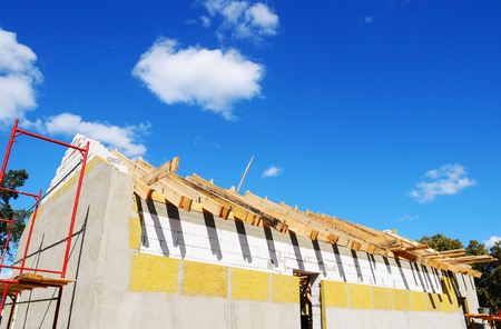 New residential construction home framing against a blue sky. Roofing construction. installation of insulation wool. white building blocks. unfinished plaster. Stock Photo