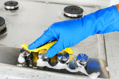 steel plate: Cleaning a gas stove. Hand protection gloves when cleaning the kitchen.