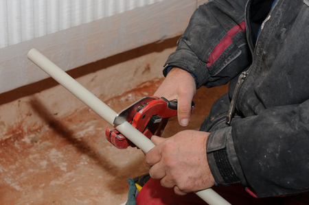 pipework: Plumber worker with scissors cuts the tube. cutting metal-plastic pipe by special red scissors. Plumber hands working with grey pipe on blurred background. plumbing pipes. individual heating system.