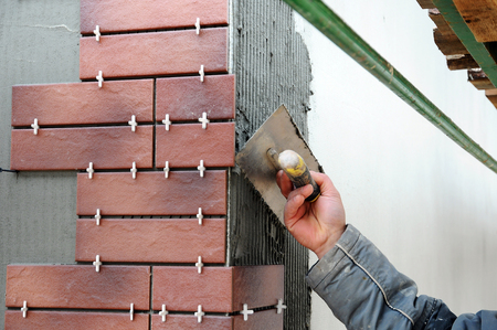 putty knives: Tiler construction worker installing decorative tiles on the facade of the building. Insulated and plastered facade. Unfinished construction. Stock Photo