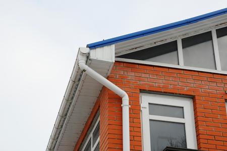 Weiße Rinne auf dem Dach des Hauses. Das rote Backsteinhaus mit großen Fenstern hautnah
