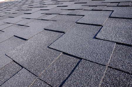 Close up view on Asphalt Roofing Shingles Background. Roof Shingles - Roofing. Bitumen tile roof. Stock Photo