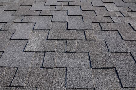 The roof shingles as a background or texture. Close up view on Asphalt Roofing Shingles Background. Roof Shingles - Roofing. Bitumen tile roof. Stock Photo