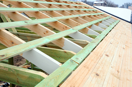 The wooden structure of the building. Wooden frame building. Wooden roof construction. photo for home. house building. Installation of wooden beams at construction the roof truss system of the house. Standard-Bild