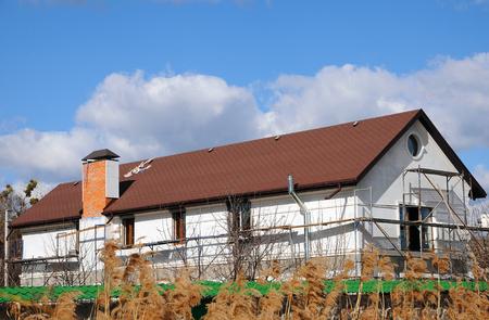 Urban house or building, facade pattern. Rain gutter. Roof Shingles - Roofing. Bitumen tile roof. Unfinished chimney system