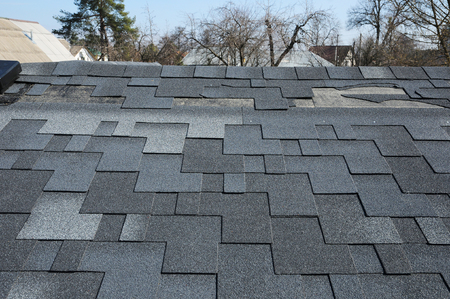 damaged roof: A close up view of shingles a roof damage. Roof Shingles - Roofing.