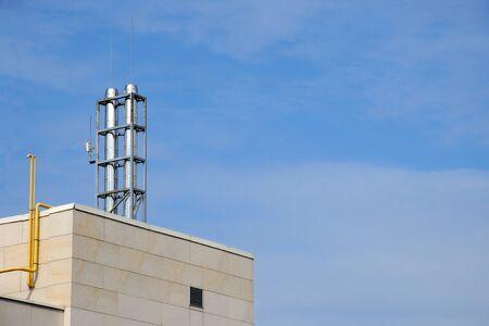 Modern chimney on the roof of hi tech home. Big metal chimney system