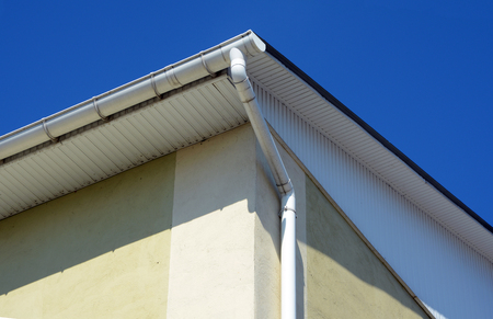 Rain gutters on a house. White gutter on the roof top of house. Guttering system Stock Photo - 89130219