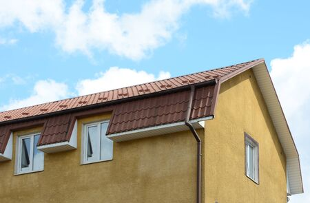 Dormer windows on metal roof. Made of metal roofing with mansard windows and rain gutter.