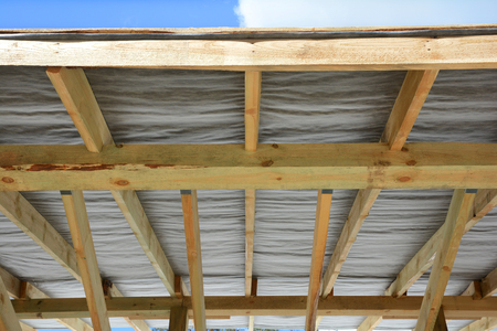 rafters: Wooden roof construction. House building. Installation of wooden beams. Installing the vapor barrier on the roof