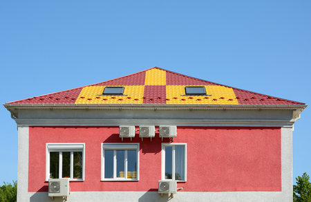 Metal roofing construction. House with a mansard and skylight. Rain gutter and snow guard. A multi-colored metal roof and many air conditioners. Stock Photo
