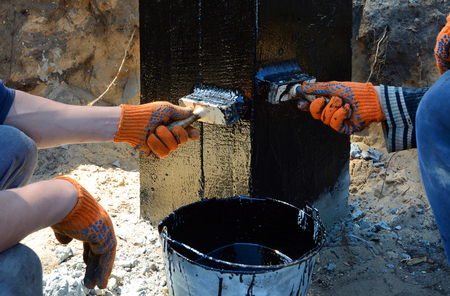 Contractor workers painting black coal tar or bitumen at a surface by the brush, A waterproofing. Foundation Waterproofing, Damp proofing Coatings.