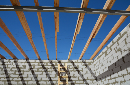 rafters: The wooden structure of the building. Wooden frame building. Wooden roof construction. photo for home. house building. Installation of wooden beams at construction the roof truss system of the house. Stock Photo