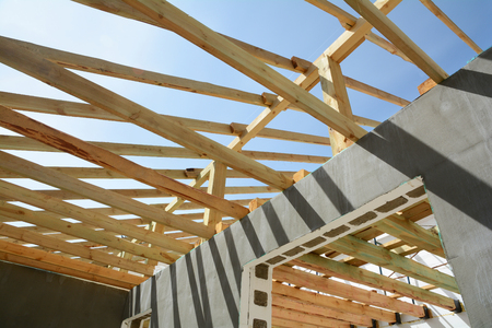 nails: Wooden frame building. Wooden roof construction. Construction of frame houses from thermoblocks. Installation of wooden beams. House building. Stock Photo