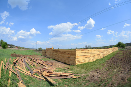A temporary wooden fence. Illegal construction in the field is fenced