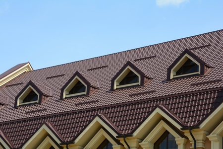 Dormer windows on metal roof. Made of metal roofing with mansard windows and rain gutter. Metal Roofing.