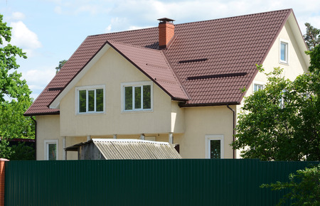 KIEV, UKRAINE - MAY 06, 2017: Metal roofing. New rain gutter system and roof protection from snow board (Snow guard) on house construction. System chimneys. Long metal fence. Editorial