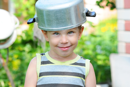 Toddler boy in with a saucepan on his head. Child with a saucepan. Happy child indulges. A child in a saucepan hat.