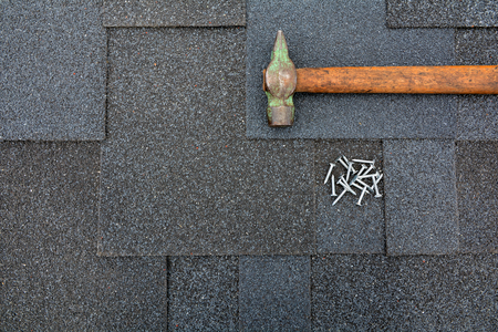 Close up view on Asphalt Roofing Shingles Background. Roof Shingles - Roofing. Asphalt Roofing Shingles Hammer and Nails