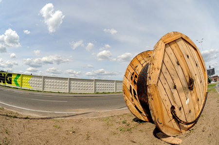A power electric cable wound on a wooden coil against a blue sky shot with a fisheye lens.