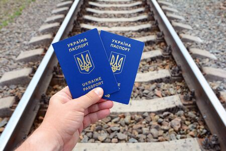 emblem of ukraine: Ukrainian blue biometric passport with identification chip on rail road background. A young mans hand holds a Ukrainian biometric passport Stock Photo