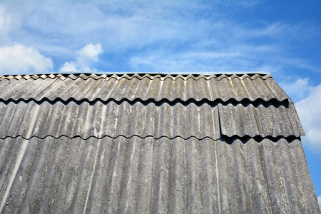 Old roof asbestos roof slates against blue sky