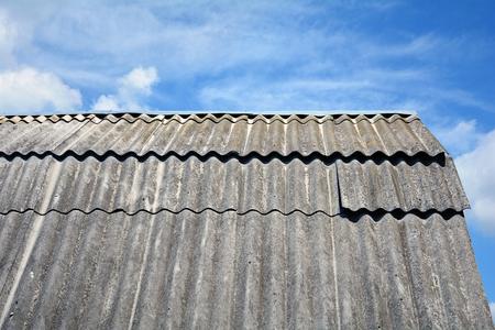 Oude dak asbest dakleien tegen blauwe hemel