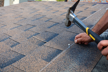 Worker hands installing bitumen roof shingles. Worker Hammer in Nails on the Roof. Roofer is hammering a Nail in the Roof Shingles. Unfinished roof.