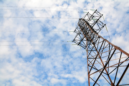 Ondersteunt hoogspanningsleidingen tegen de blauwe lucht met wolken. Elektrische industrie van Europa. Stockfoto