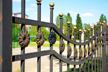 Beautiful wrought fence. Image of a decorative cast iron fence. Metal fence close up.