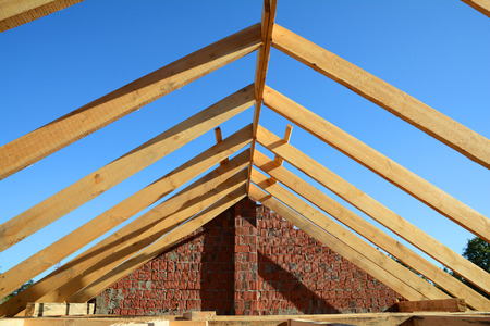 Wooden roof construction. Unfinished House building. Installation of wooden beams at the construction of the truss system of the house.