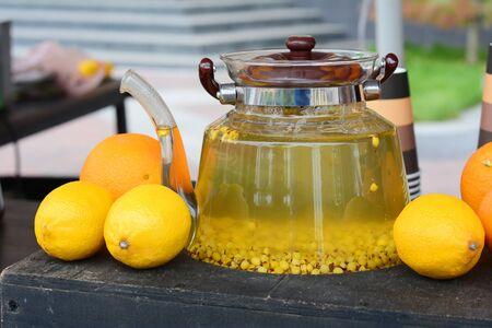 Glass teapot with sea-buckthorn berry tea. Sea-buckthorn tea at the food fair.