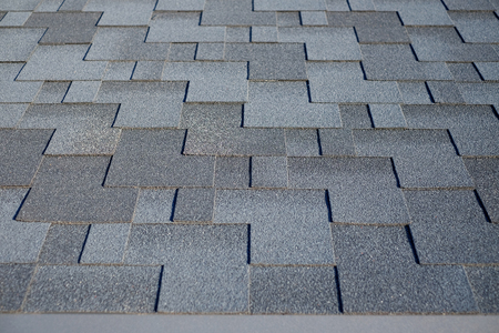 Close up view on Asphalt Roofing Shingles Background. Roof Shingles - Roofing. Bitumen tile roof. 版權商用圖片