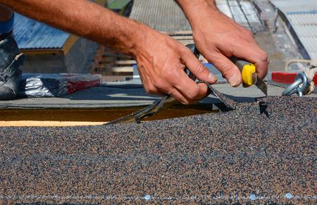 Reparación del techo cortando fieltro o tejas de betún durante los trabajos de impermeabilización. Foto de archivo - 96102401