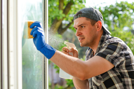 Young window cleaner with a spray detergent onto glass