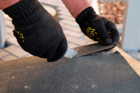 Repairing of roof by cutting felt for installing bitumen shingles during waterproofing works. Stock Photo