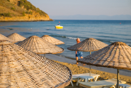 Beach umbrellas and chaise lounges with sea and sky in the background.
