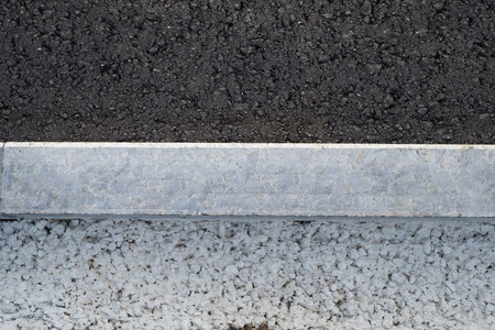 New asphalt road, curbs and of gravel and concrete.