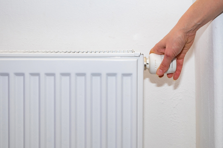 Female hand regulates the thermostat knob on the white heating radiator with at home a cold season. Banco de Imagens