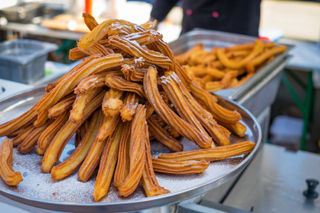 Delicious churros sticks deep fried and dusted with powdered sugar. Sweet street food.