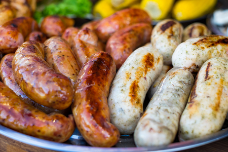 Fresh sausage and hot dogs grilling outdoors on a gas barbecue grill. Standard-Bild - 117513025