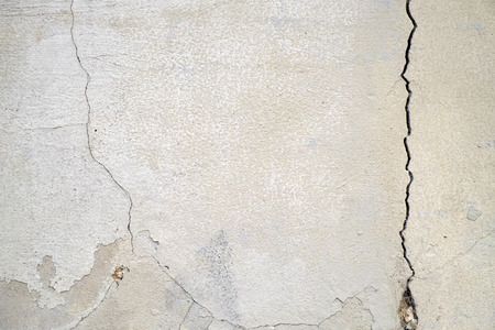 Old foundation and plaster wall with cracks. Building requiring repair closeup. Stockfoto