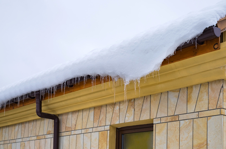 Snow and ice on the roof and rain gutter. Stok Fotoğraf